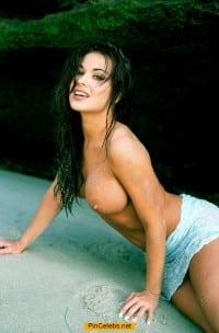 Brunette Carmen Electra topless on a beach