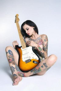 naked tattooed young brunette with guitar