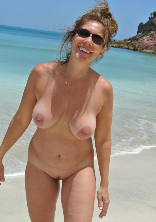 MILF chick romps along a nude beach in her birthday suit