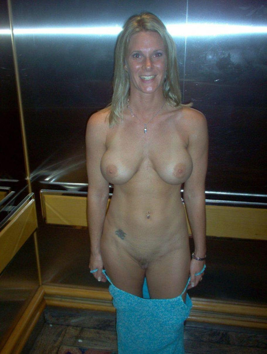 Smiling blonde off her dress in the elevator